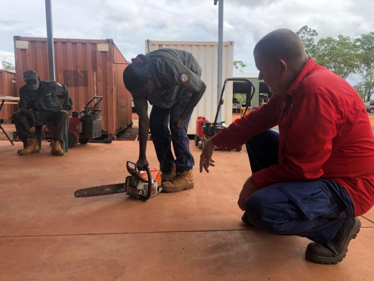 Train Safe NT's Ian van Munster showing Florence Biridjala how to use a chainsaw, with Peter Djigirr looking on.